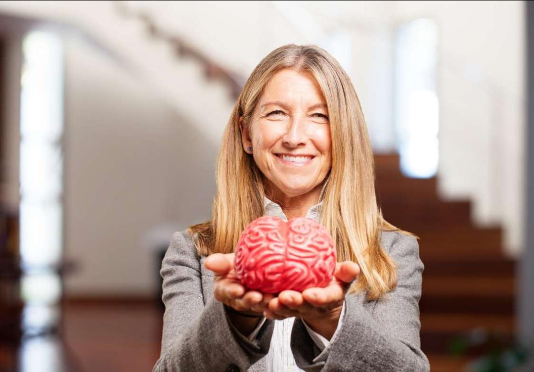 Žena s dlouhými vlasy drží v rukách plastový model mozku