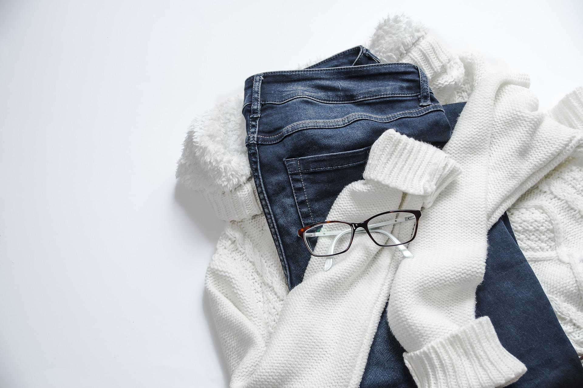 Bílý svetr, modré džíny a brýle