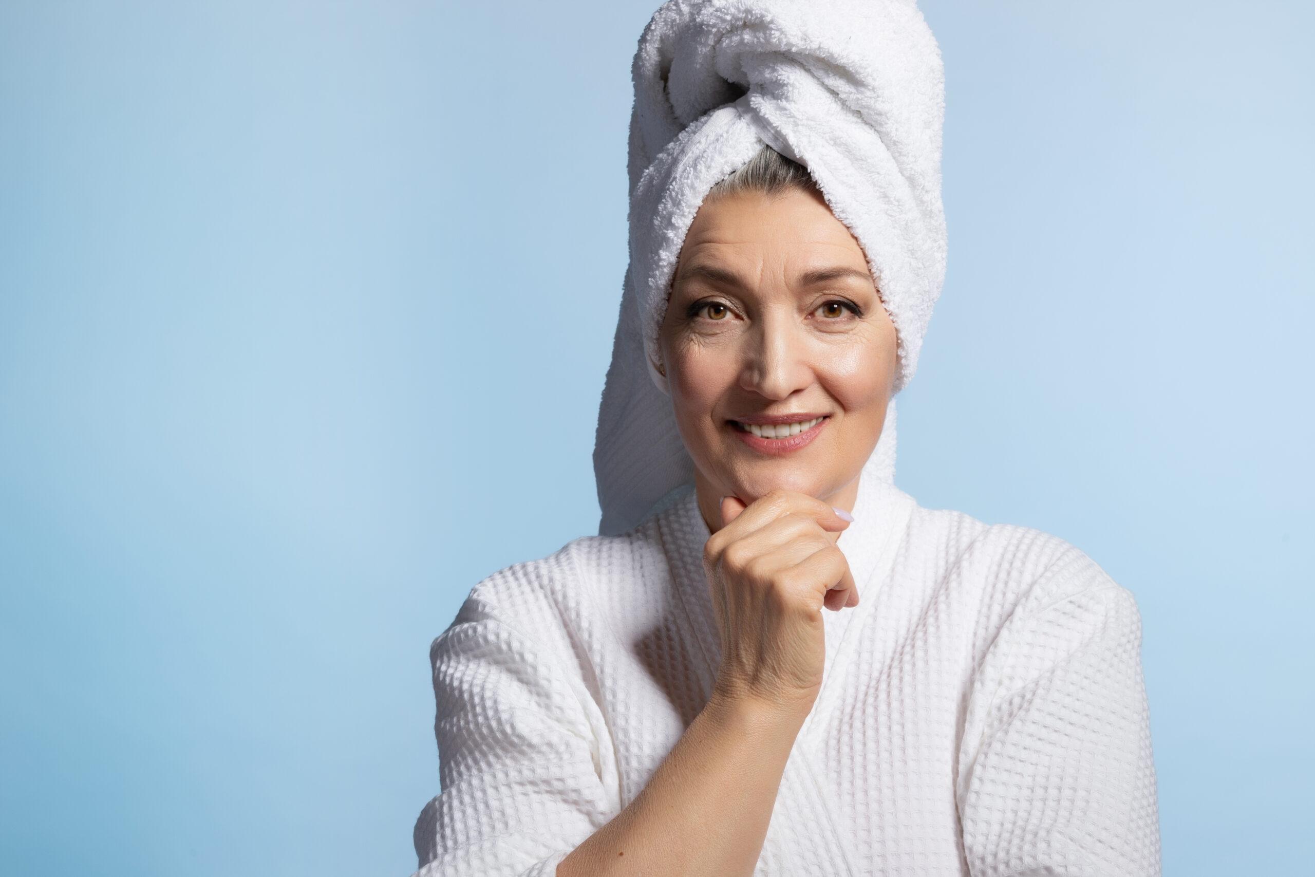 Žena s ručníkem na hlavě v salonu