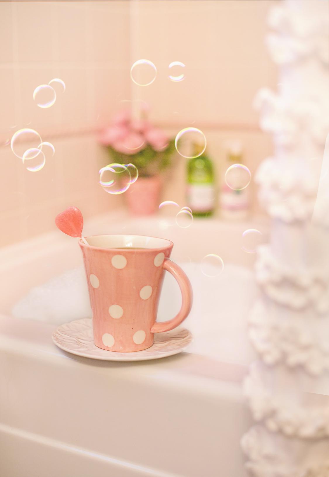 růžový hrnek s puntíky na vaně, bublinky poletující kolem