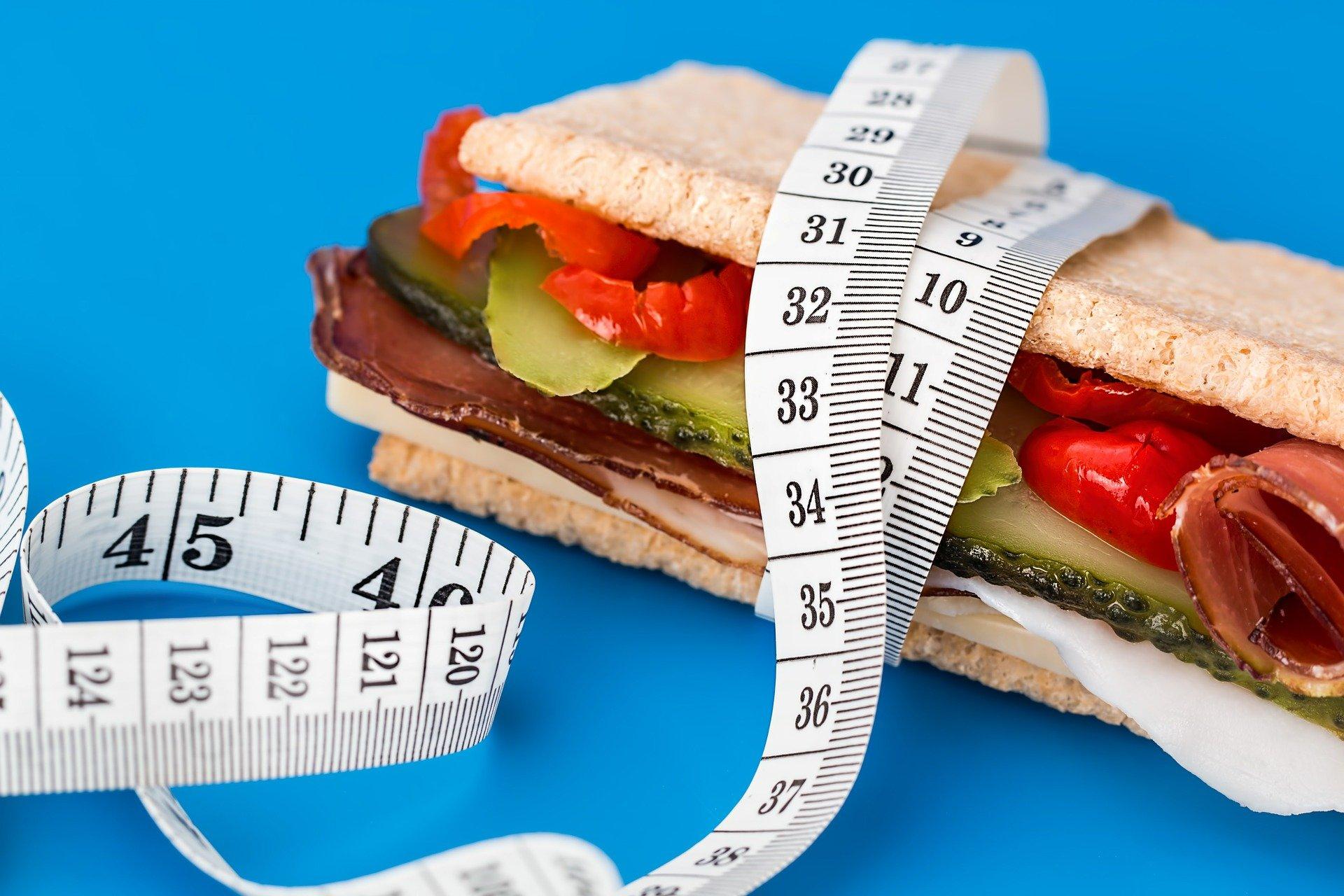 sandwitch odmotaný centimetrem na modrém pozadí