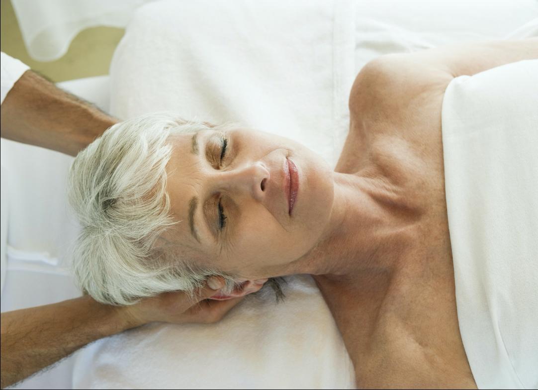 žena ležící na zádech a ruce masírují její hlavu