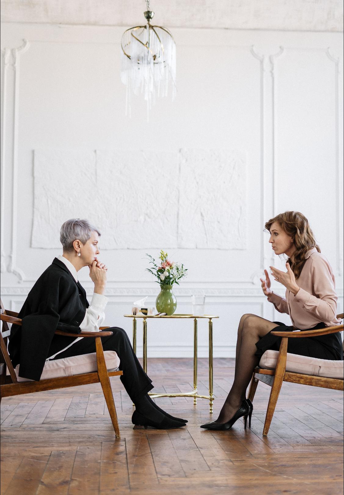 dvě ženy sedí proti sobě v místnosti na křeslech
