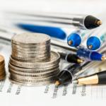 komínek drobných peněz na stole spolu s tužkami