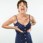 žena v puntíkatých šatech se drží pod prsy a směje se svému stylu